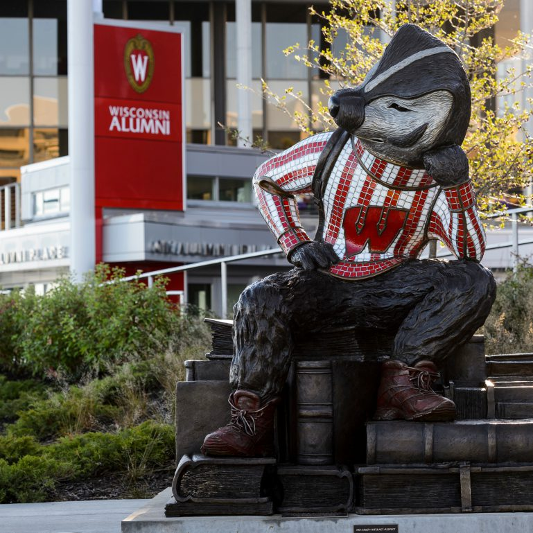 """""""Well Red,"""" a sculpture by artist Douwe Blumberg of a studious-looking UW-Madison mascot Bucky Badger sitting atop a pile of books, is pictured at Alumni Park at the University of Wisconsin-Madison during the autumn morning of Oct. 8, 2017. In the background is One Alumni Park. The newly-opened park, part of the Wisconsin Alumni Association (WAA), is located between the Memorial Union and Red Gym (Armory and Gymnasium) overlooking the Lake Mendota shoreline. In the background is One Alumni Place. (Photo by Jeff Miller / UW-Madison)"""